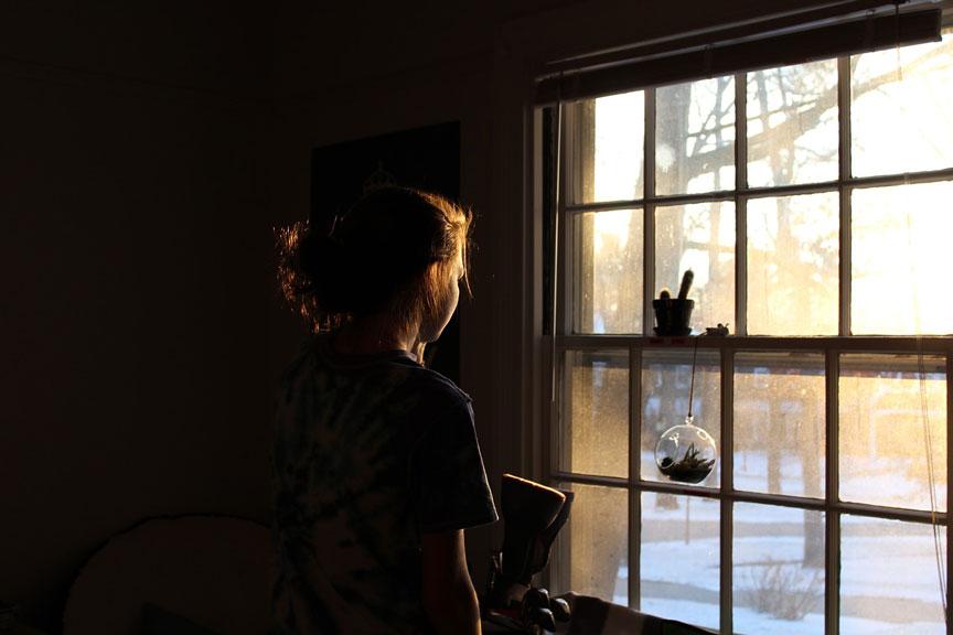 Kvinde der eftertænksomt kigger ud af vinduet